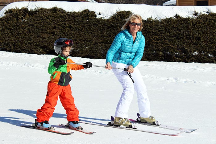 une mamie apprend à son petit fils à skier grâce à la technique du bâton.