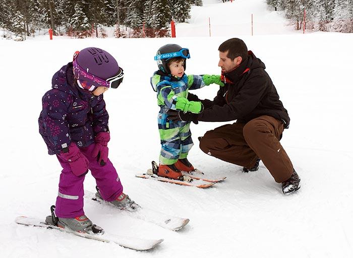 papa qui apprend le ski à sa fille et son garçon
