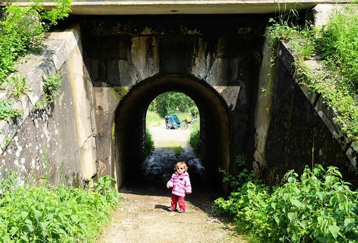 Erin devant le petit tunnel avant de la franchir avec les vélos et la carriole.