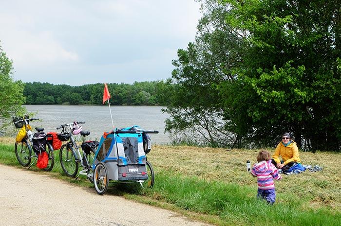 Pique-nique sur l'herbe en famille à côte des vélos et de la carriole, en bord de