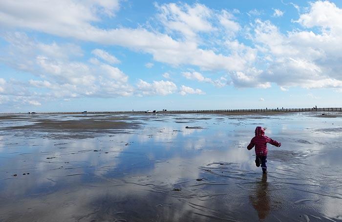 Erin court en bottes sur le sable mouillé en Camargue au bord de mer