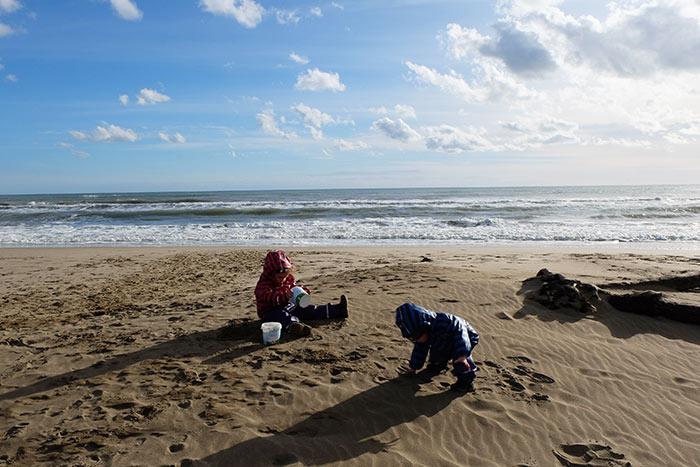 les enfants font des pâtés de sable au bord de la mer dans le sud de la France