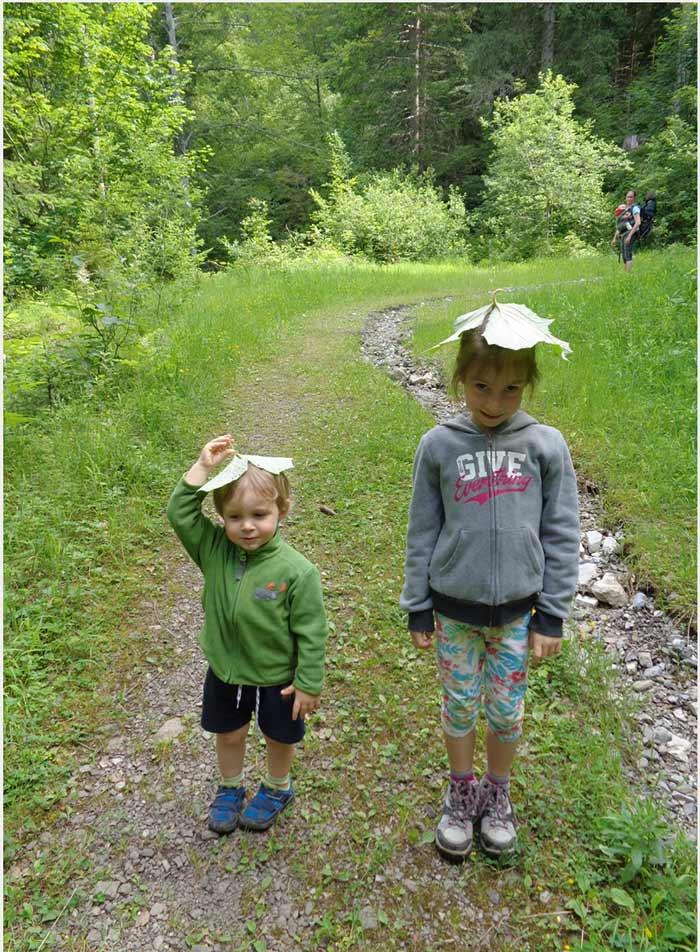 les enfants se fabriquent des chapeaux en feuilles trouvées lors de la rando