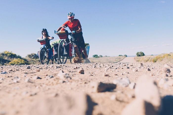 olivier et adeline poussent leur vélo sur la piste caillouteuse