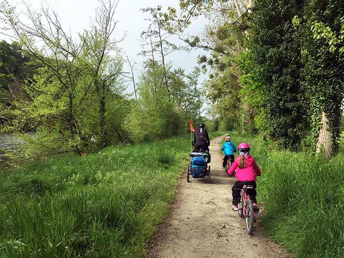 sur le chemin à vélo en famille avec la remorque