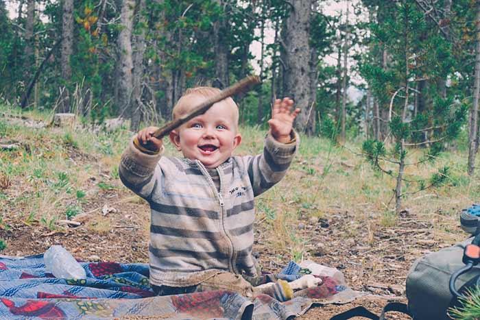 bébé joue avec un bâton au bivouac en forêt