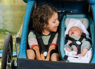 une enfant et un bébé dans une remorque vélo