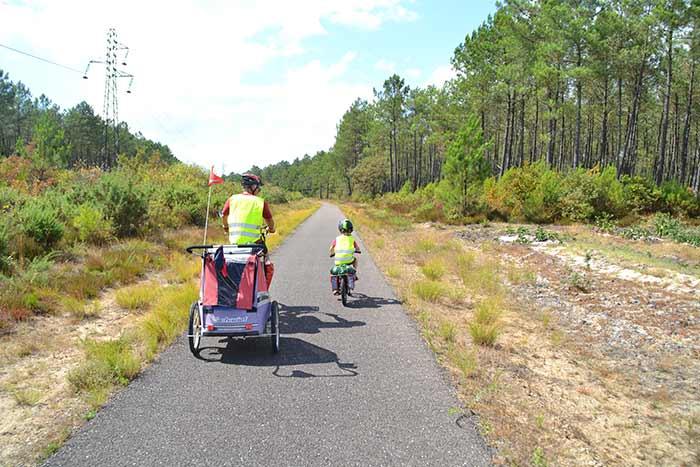 piste cyclable parent avec remorque et enfant