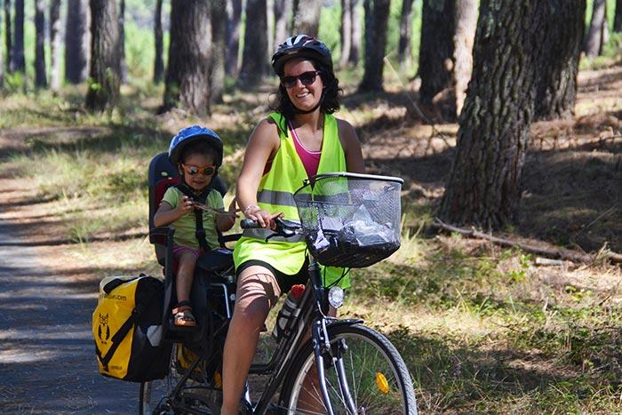 portrait maman et l'enfant sur le vélo dans le siège bébé sur la voie verte