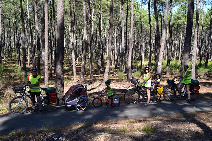 portrait de famille sur la voie verte à travers la forêt de pins