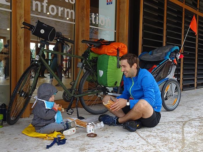 papa et son enfant avec la remorque vélo