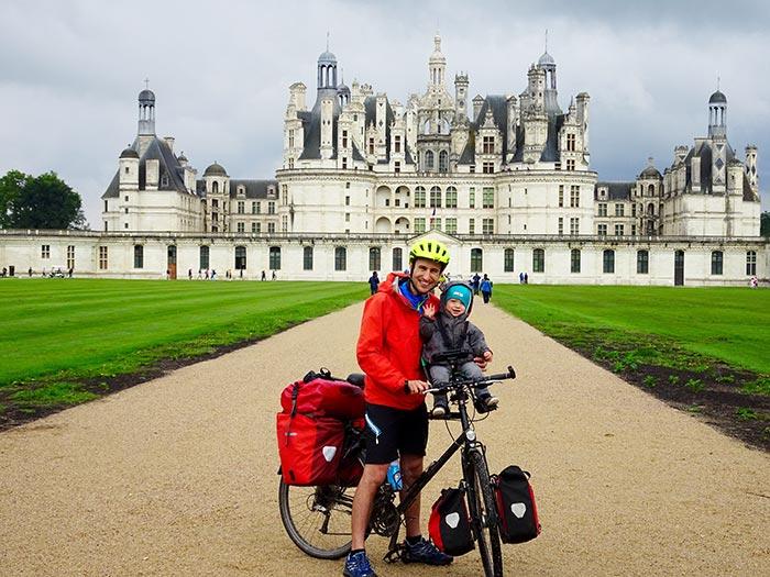 papa et enfant en vélo devant le château de Chambord