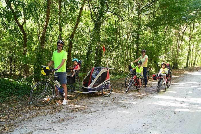 photo d'une famille sur la voie verte Passa Païs, avec remorque et siège vélo