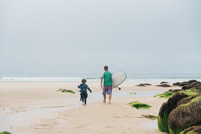 papa et son fils vont surfer sur la plage de la palue