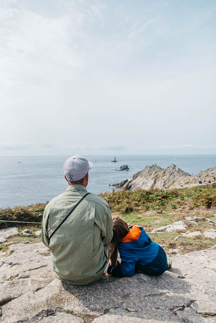 Papa et son fils contemplent le paysage à la Pointe du Raz en Bretagne