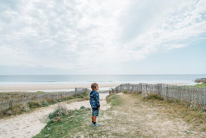 Petit garçon regarde l'océan en Bretagne.