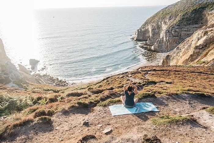 Femme en séance de yoga pour au Cap de la Chèvre dans le Finistère