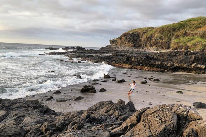 enfant qui joue sur une plage de sable noir sur l'île de la Réunion