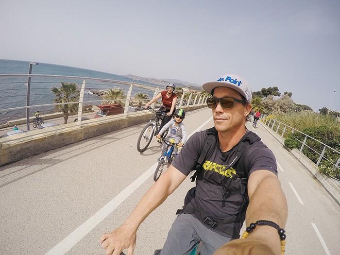 """famille qui fait du vélo sur la piste cyclable du Parc Côtier de la Riviera dei Fiori """"Area 24"""" en Italie"""