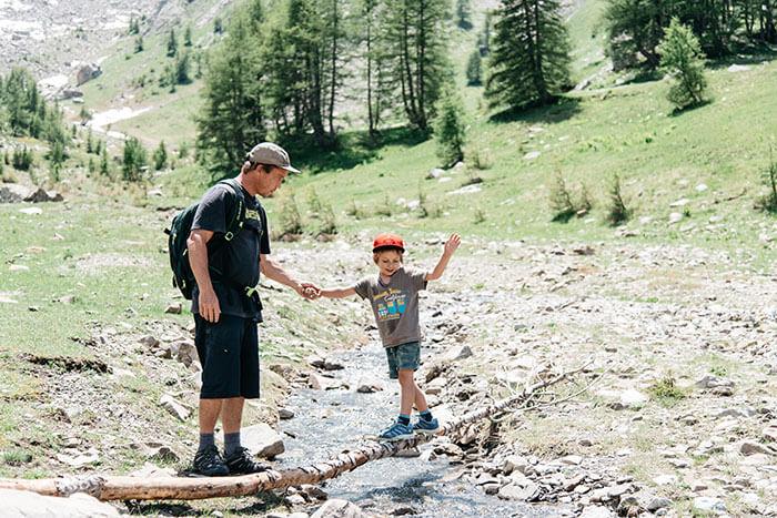 papa et son enfant traversent un torrent durant une randonnée en famille dans le val d'Allos en Provence Alpes Côte d'Azur