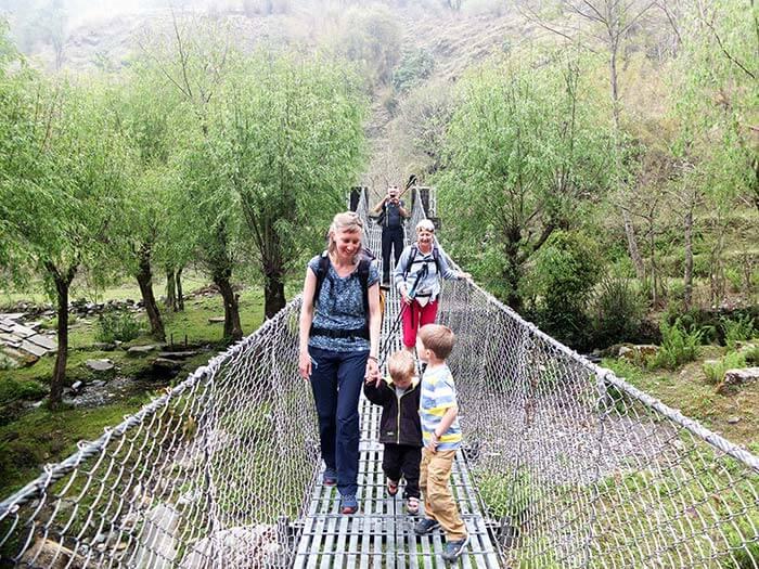 famille sur un pont suspendu le long d'un trek au Népal