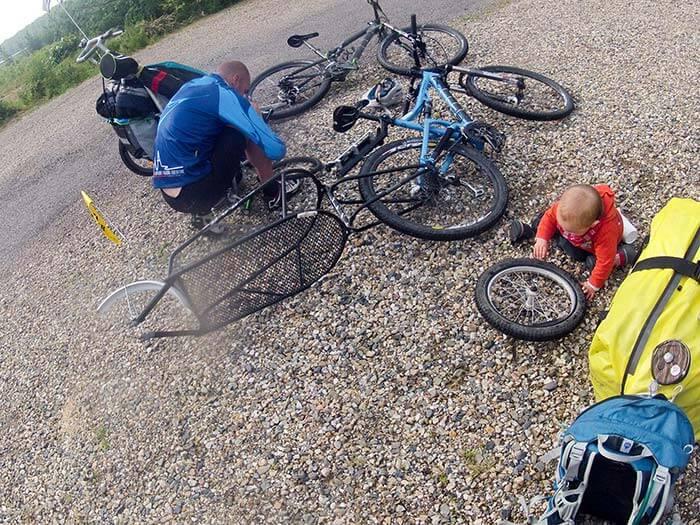 un papa et son enfant répare un e crevaison durant une sortie cyclo
