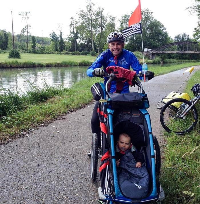 papa et son enfant dans une remorque vélo en mode poussette
