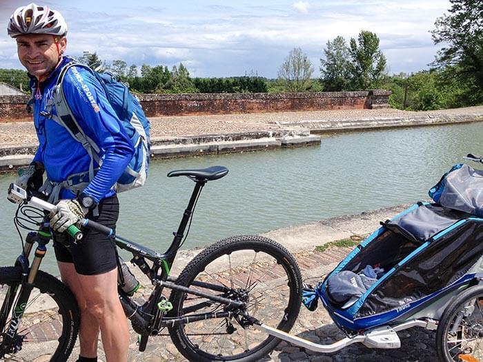 Photo de David, son vélo et sa remorque sur le Canal Latéral en bord de Garonne