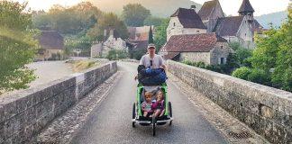 papa et et ses enfants en randonnée avec la carriole dans la Vallée du Célé sur les Chemins de Saint Jacques de Compostelle