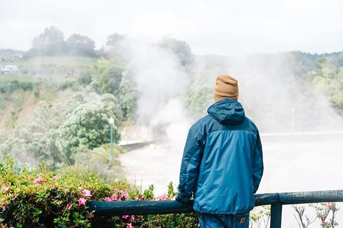 homme devant les fumerolles de Furnas aux Açores sur l'île de Sao Miguel