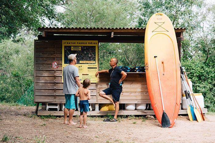 une famille de clients échange avec le chef de base nautique kayak paddle fréjus