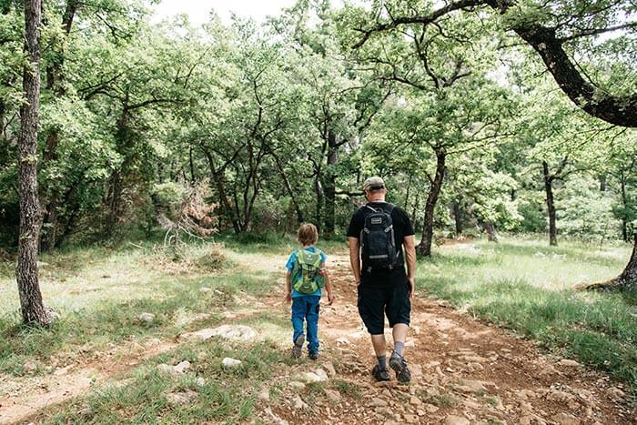 enfant et son papa en randonnée en forêt sur un chemin de terre à Montauroux