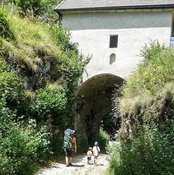famille en balade passe sous une porte fortifiée