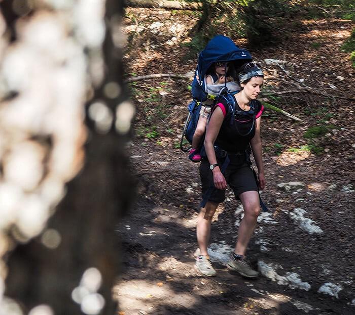 fille portée sur le dos de sa maman avec le nouveau porte bébé Deuter Kid Comfort Pro en promenade en forêt