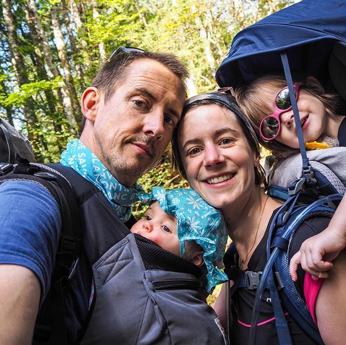 portrait de famille : papa, maman et leurs 2 petites filles dans la nature