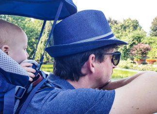 papa et son petit garçon porté dans un porte bébé de randonnée regardent la vue dans un jardin