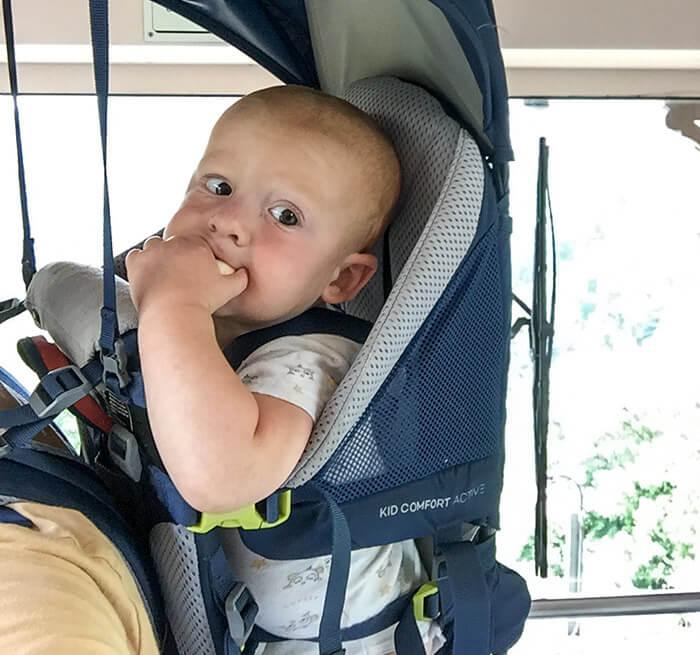 enfant qui mange installé dans le porte bébé de randonnée Deuter Kid Comfort Active 2019