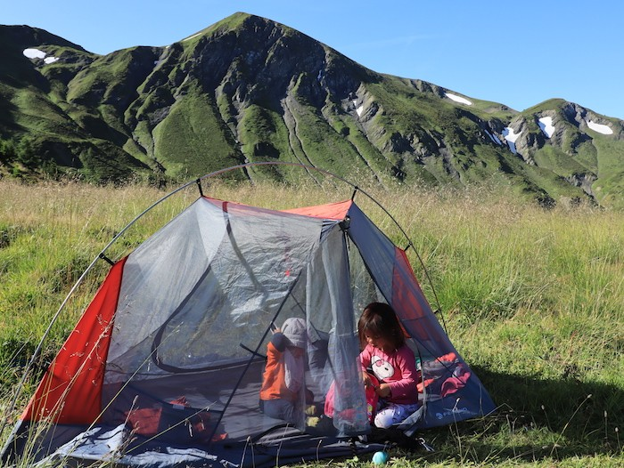 enfants dans une tente en bivouac dans les alpes