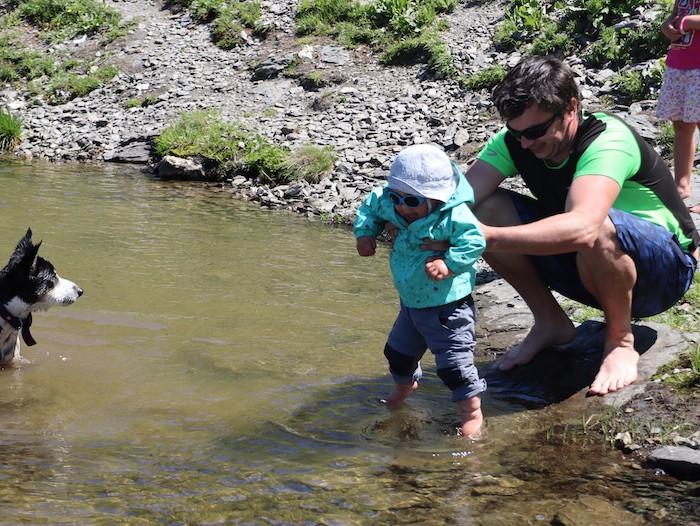 enfant et parents dans une rivière en randonnée