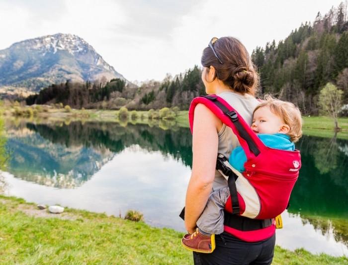 maman porte son bébé dans un porte bébé physiologique en randonnée